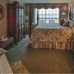 Rehoboth Beach DE Victorian Hotel deluxe room with large bed, wardrobe, tub, and balcony