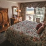 Rehoboth Beach DE Victorian styled hotel king room with large bed, wardrobe, and balcony