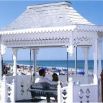 White Gazebo with a swing seating a couple overlooking the ocean