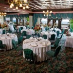 Large dining room with green chairs and white rounded tables for wedding events