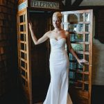 Bride in wedding dress in vintage telephone booth