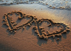 Two hearts drawn in wet sand with water rising up