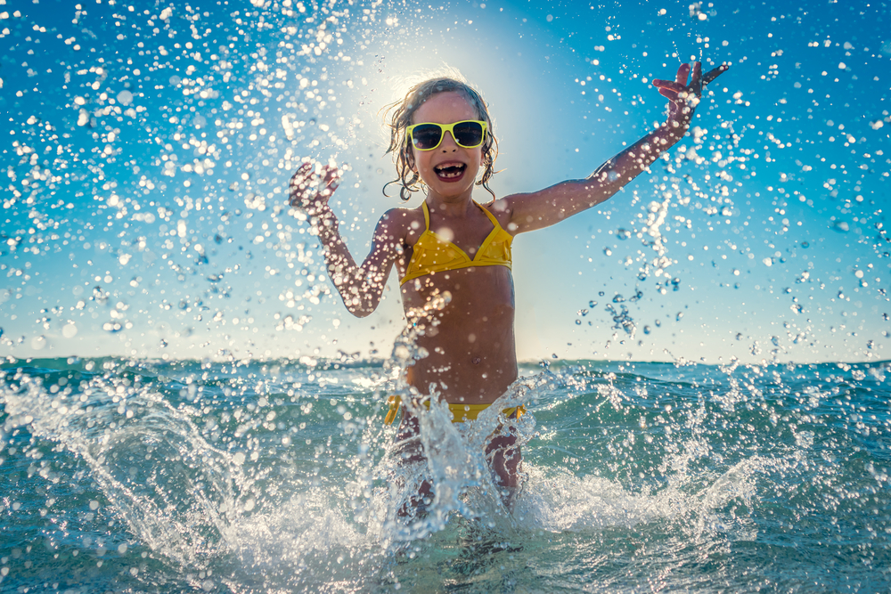 female child splashing in ocean water with yellow sunglasses and bathing suit