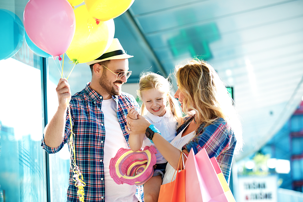 Couple holding toddler daughter with baloons and shopping bags