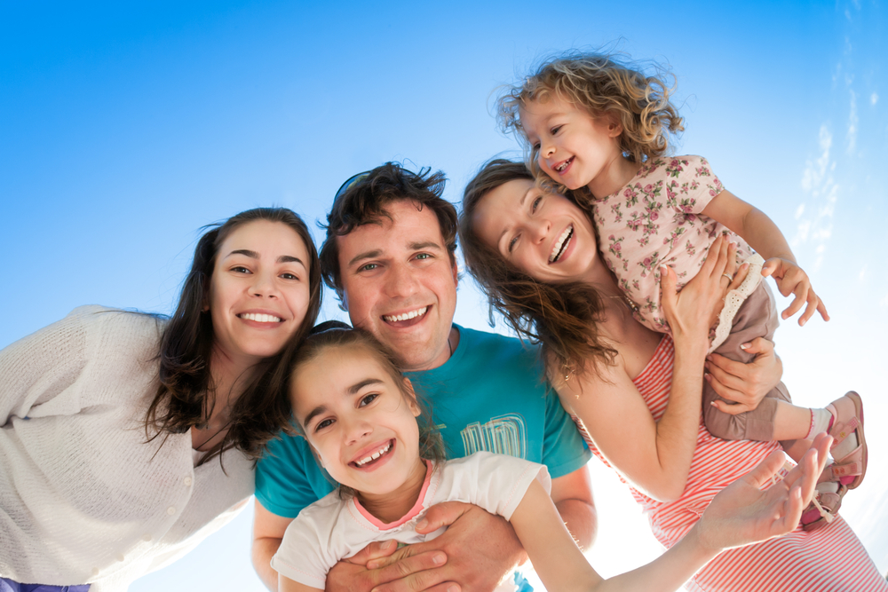 family of couple and three kids smiling with a sky colored background