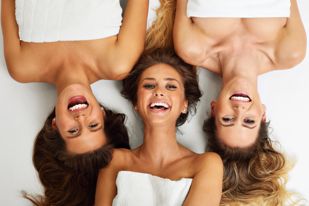 three women laying on hotel bed smiling and laughing