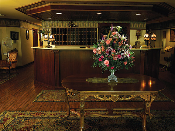 picture of hotel lobby with large flower arrangements on center table and lobby desk behind it
