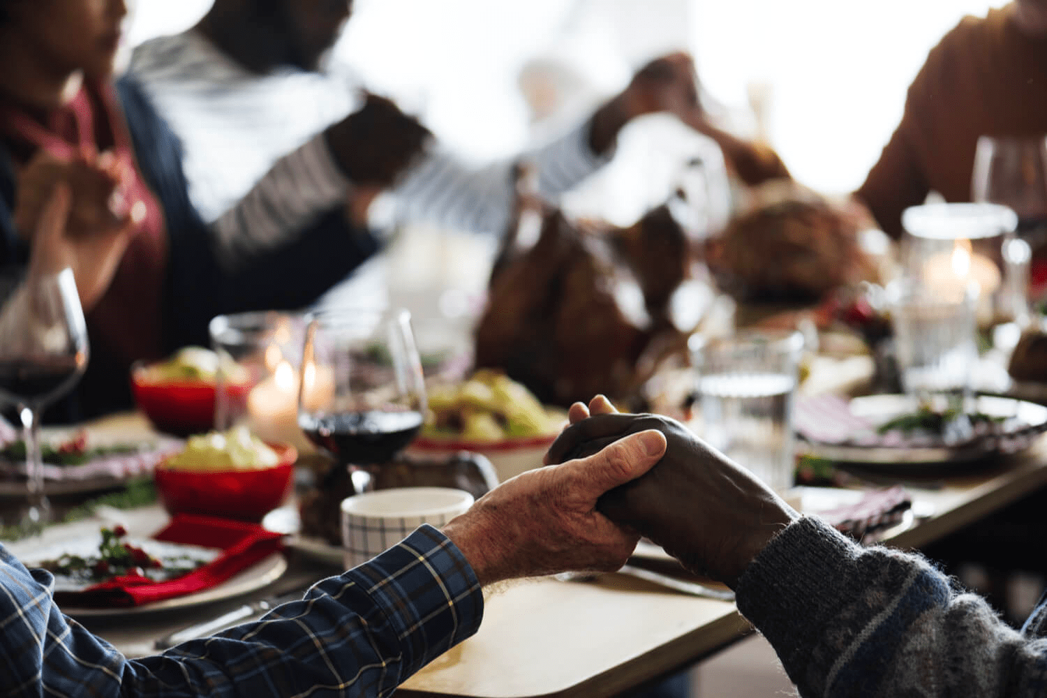 family gathered around table holding hands for prayer before thanksgiving dinner